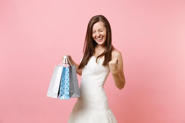 買い物後に購入したマルチカラーのパッケージバッグを持っている勝者のように拳を食いしばっている白いドレスを着た大喜びの女性