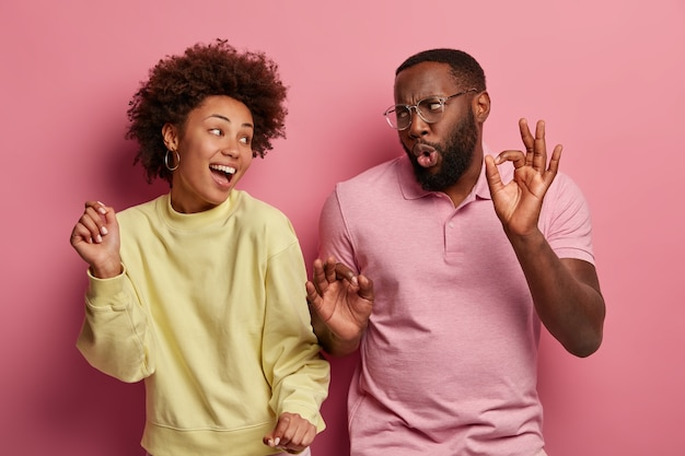 Overjoyed woman and man with dark skin have upbeat mood, dance at disco party, raise arms and move with rhythm of music, wear casual clothes, isolated on pink space. people