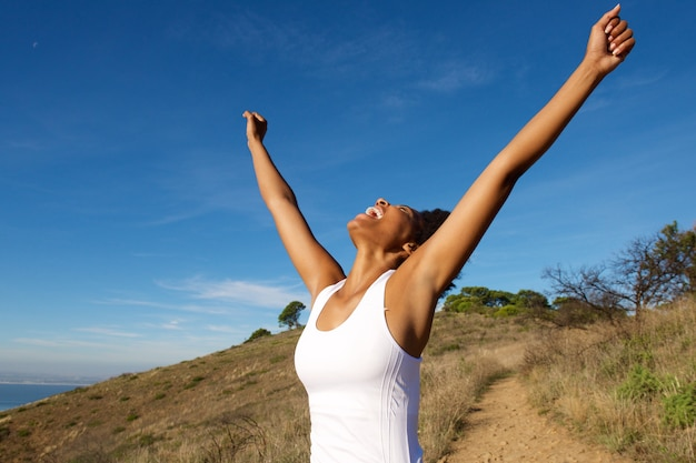 Overjoyed woman outdoors with her arms wide open