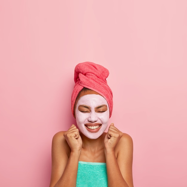 Overjoyed woman raises clenched fists, being in high spirit, has beauty treatments at home, wears towel, keeps eyes shut from pleasure