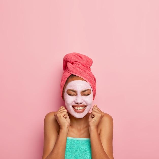 Обрадованная женщина поднимает сжатые кулаки в приподнятом настроении, проходит косметические процедуры дома, носит полотенце, закрывает глаза от удовольствия.