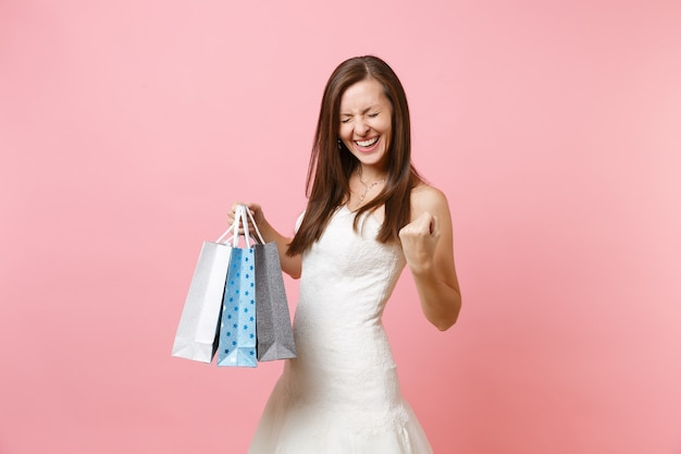 Overjoyed woman in white dress clenching fists like winner holding multi colored packages bags with purchases after shopping