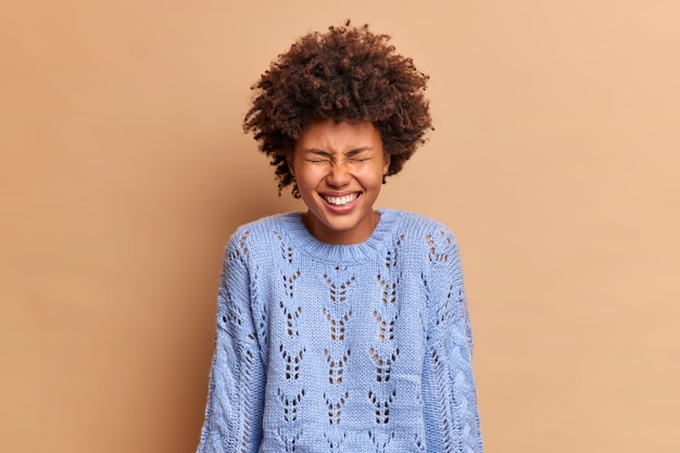 곱슬 머리를 가진 기뻐하는 여자는 긍정적 인 웃음과 눈을 감고 하얀 치아가 갈색 벽 위에 고립 된 캐주얼 니트 점퍼를 착용하고 있습니다.