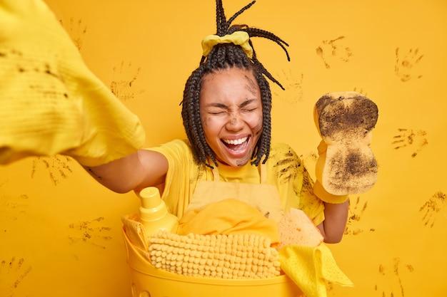 ドレッドヘアを持つ大喜びの女性がカメラで腕を伸ばして笑う黄色い壁に隔離された洗濯かごの近くで汚れたスポンジのポーズを喜んで保持します