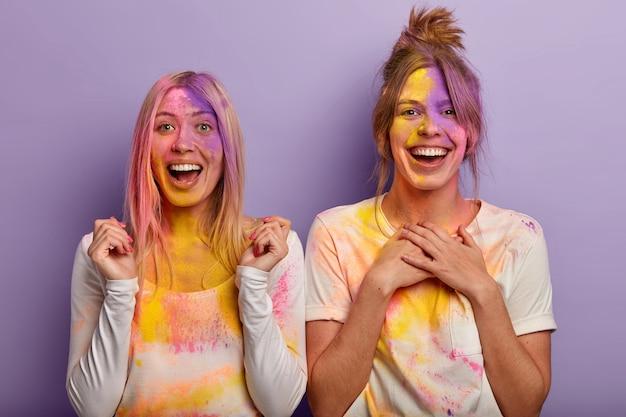 Donne felicissime spalmate di cipria colorata, si divertono durante il festival of colours in india, stringono i pugni, tengono entrambi i palmi sul petto, indossano abiti bianchi casual, gioiscono in arrivo la primavera. vacanza holi