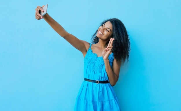 大喜びの若いアフリカの民族の女性は、彼女の伸ばした腕にスマートフォンを持って、自分撮りをしながら、心から笑っています