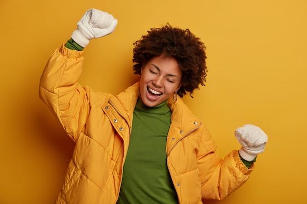 기뻐하는 젊은 아프리카 계 미국인 여성이 적극적으로 춤을 추고 따뜻한 겨울 코트와 장갑을 끼고 긍정적 인 표정을 지으며 노란색 배경에 서 있습니다.