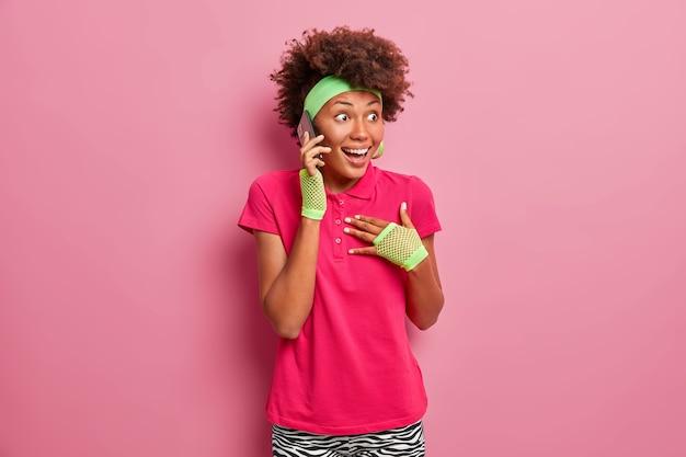 La giovane donna afroamericana felicissima si sente eccitata, guarda con espressione felice sorpresa, trattiene il respiro, parla tramite smartphone, sussulta meravigliata, riceve ottime notizie