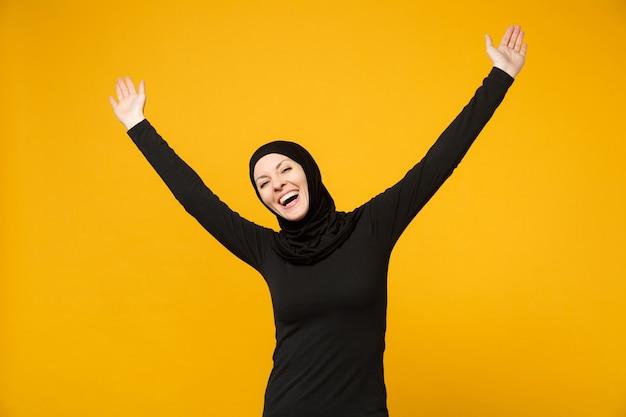 勝者のジェスチャーをしているヒジャーブの黒い服を着た若いアラビアのイスラム教徒の女性を大喜びし、黄色の壁に隔離されたはい、肖像画と言います。人々の宗教的なライフスタイルの概念。