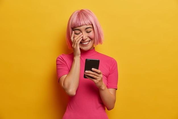 Overjoyed young asian lady has bob hairstyle, laughs sincerely at message in social network, enjoys mobile communication, reads funny news
