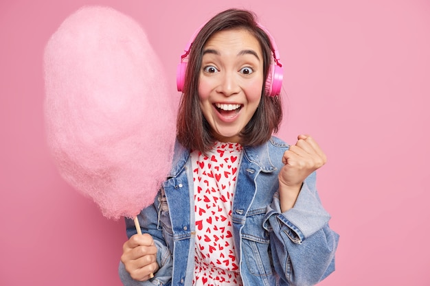 大喜びの若いアジア人女性は、素晴らしいニュースがくいしばられた握りこぶしを上げるのを聞いて、勝利を広く祝います。おいしい甘くした綿菓子を食べ、屋内でワイヤレスヘッドフォンポーズを介して音楽を聴きます。
