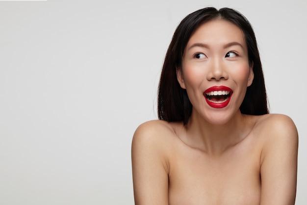 Обрадованная молодая красивая темноволосая женщина с праздничным макияжем, пожимая плечами и счастливо глядя в сторону с широкой улыбкой, изолирована на белой стене