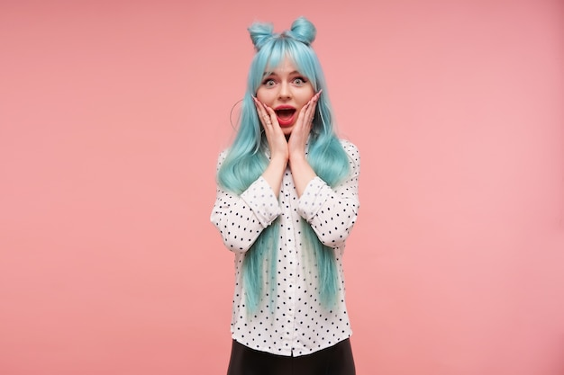 Overjoyed young blue haired pretty female rounding eyes and holding face with raised palms while looking, wearing elegant clothes while posing