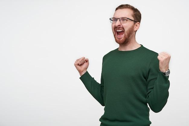 彼のお気に入りのチームを応援し、幸せに拳を上げている間、興奮して叫んでいる緑のセーターを着た若い茶色の髪のひげを生やした男は、孤立して大喜びしました