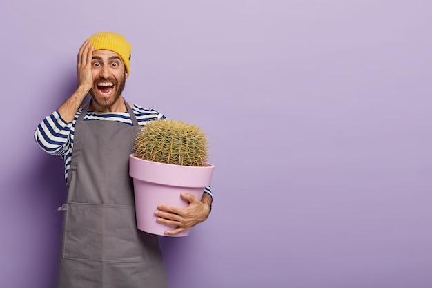 Il giovane uomo caucasico felicissimo tiene il cactus in vaso, vestito in uniforme da lavoro speciale