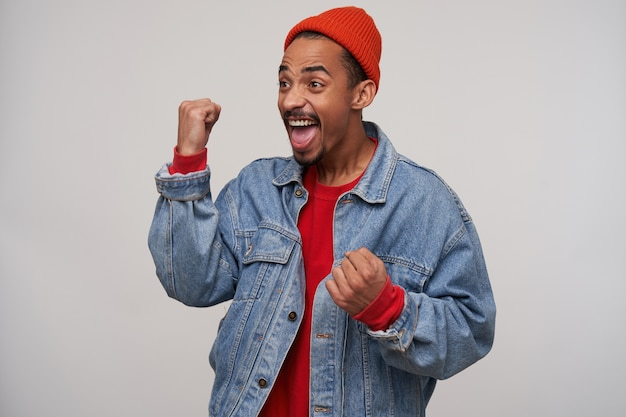 Overjoyed young dark skinned bearded brunette guy screaming happily with raised fists, wearing red cap, pullover and blue jeans coat while standing over white wall
