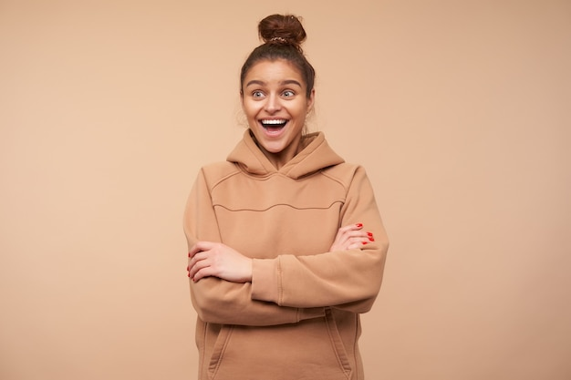Overjoyed young good looking brunette woman with natural makeup crossing hands on her chest while laughing excitedly with wide mouth opened, posing over beige wall