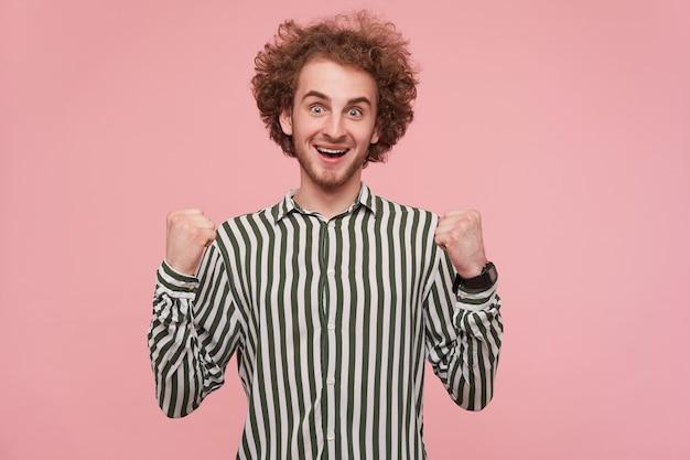 Felicissimo giovane bel ragazzo dai capelli rossi ricci con acconciatura casual che guarda l'obbiettivo con gli occhi spalancati e la bocca aperta, alzando felicemente i pugni mentre posa sul muro rosa