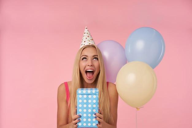 Giovane signora bionda dai capelli lunghi felicissima che è eccitata e sorpresa di ricevere regali di compleanno, avendo momenti allegri nella sua vita durante la festa di compleanno, in posa su sfondo rosa