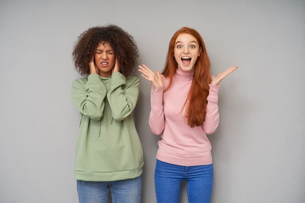 Overjoyed young long haired redhead woman raising emotionally her palms and screaming excitedly while her dark haired curly friend covering her ears and frowning face, isolated over grey wall