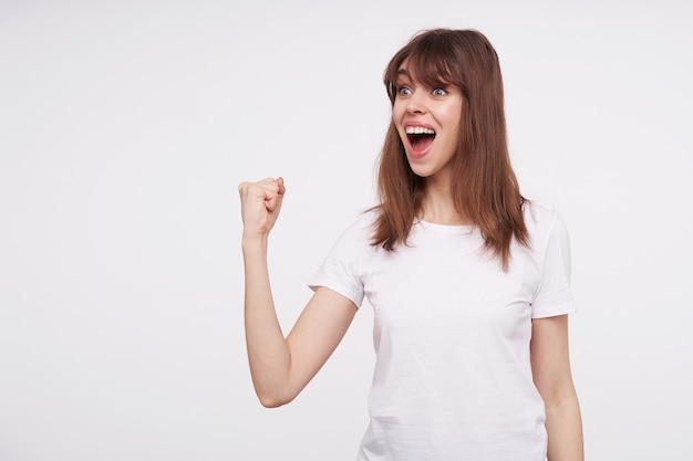 Overjoyed young lovely brown haired female with natural makeup showing her fist and looking amazedly aside with opened mouth, wearing basic white t-shirt over white wall