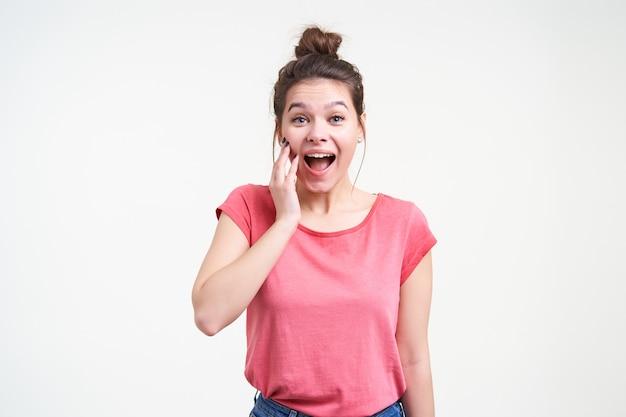Felicissima giovane bella donna castana con trucco naturale che alza emotivamente la mano al viso mentre guarda con entusiasmo la fotocamera, isolata su sfondo bianco