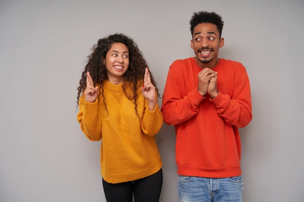 Overjoyed young lovely dark skinned brunette couple looking excitedly on each other and keeping hands raised, posing over grey background in casual clothes