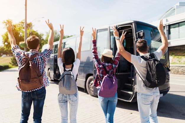 Обрадованные молодые люди ждут поездки на автобусе.