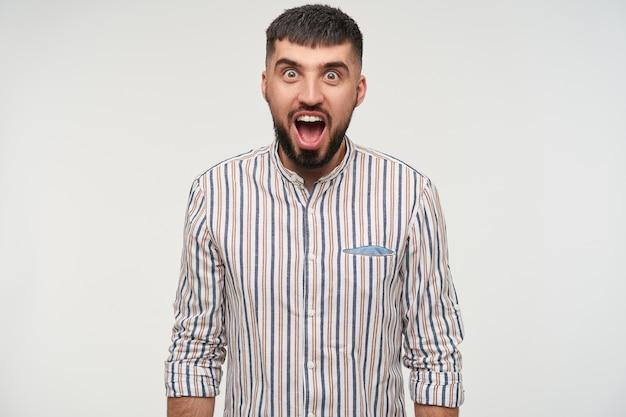 Felicissimo giovane maschio piuttosto moro con taglio di capelli corto che arrotonda gli occhi marroni mentre guarda sorpreso, tenendo le mani lungo il corpo mentre posa sul muro bianco