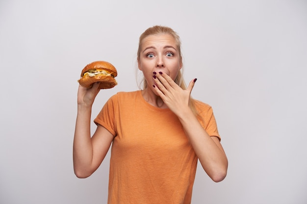 Overjoyed young pretty long haired blonde lady holding delicious burger in raised hand and looking at camera with wide eyes opened, covering her mouth with palm over white background