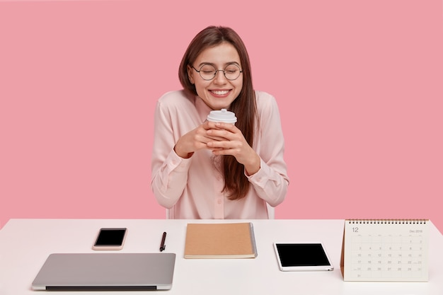 Overjoyed young student has dreamy expression, holds disposable cup with coffee, has break at coworking space, surrounded with modern laptop, tablet