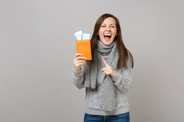 Overjoyed young woman in gray sweater, scarf pointing index finger on passport boarding pass ticket isolated on grey background. healthy fashion lifestyle people sincere emotions, cold season concept.
