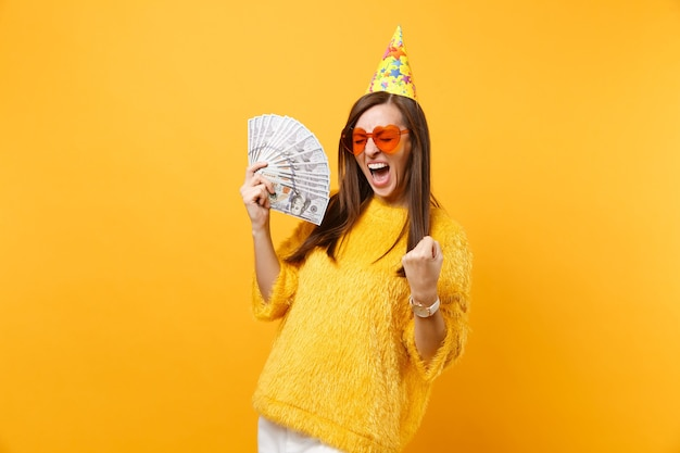 Overjoyed young woman in orange heart glasses birthday hat doing winner gesture, saying yes holding bundle lots of dollars cash money isolated on yellow background. people sincere emotions, lifestyle.