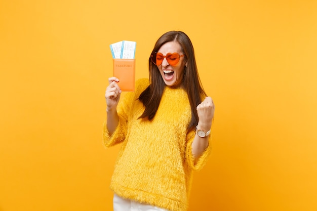 Overjoyed young woman in orange heart glasses screaming, doing winner gesture holding passport boarding pass tickets isolated on yellow background. people sincere emotions lifestyle. advertising area.