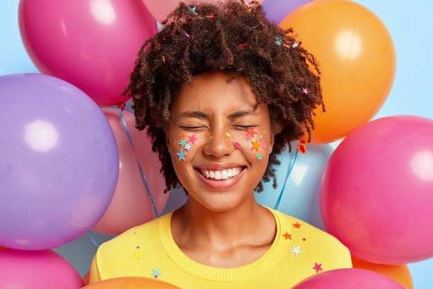 Giovane donna felicissima in posa circondata da palloncini colorati compleanno
