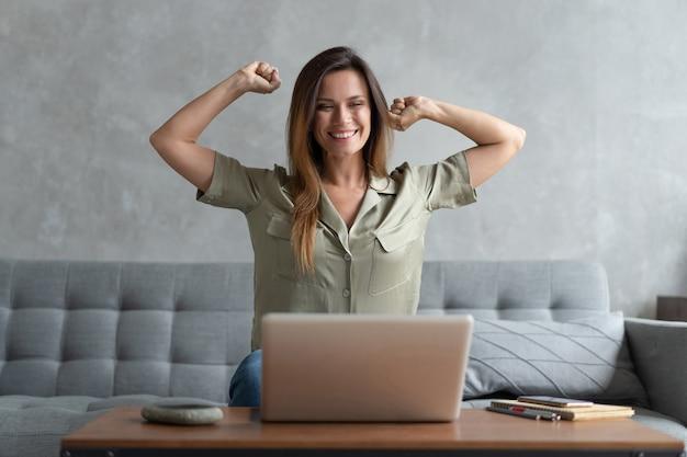 Обрадованная молодая женщина сидит на диване дома, торжествует, получает приятное электронное письмо или читает хорошие новости на ноутбуке в интернете, счастливая женщина-миллениал чувствует себя взволнованной, выигрывая в лотерею на компьютере, концепция вознаграждения