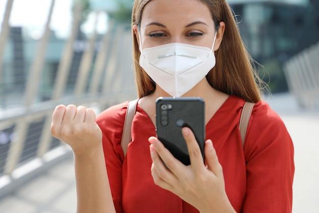 Обрадованная молодая женщина с поднятым кулаком и защитной маской kn95 читает сообщение по мобильному телефону, выражающее радость по поводу хороших новостей.