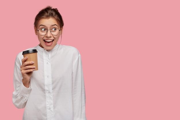 ピンクの壁に向かってポーズをとってメガネで大喜びの若い女性