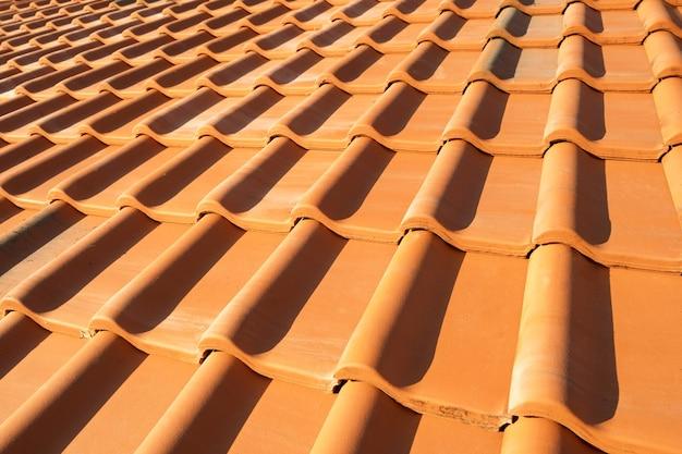 住宅の屋根を覆う黄色のセラミック屋根瓦の重なり合う列。