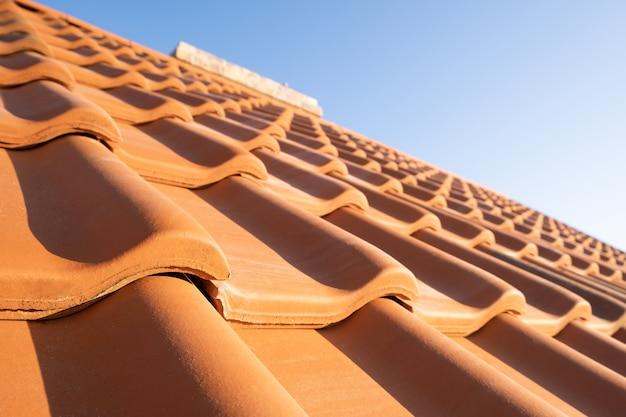 주거용 건물 지붕을 덮고 있는 노란색 세라믹 지붕 타일이 겹쳐져 있습니다.