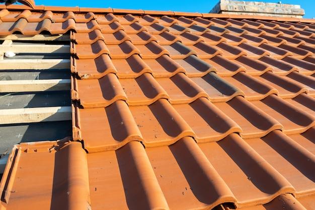 Перекрывающиеся ряды желтой керамической черепицы на деревянных досках, покрывающих крышу строящегося жилого дома.
