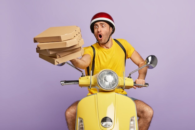 Overload busy deliveryman driving yellow scooter while holding pizza boxes