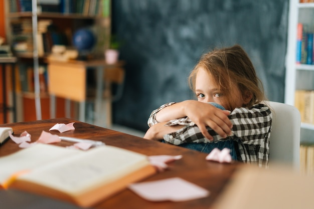 Overload upset primary child school girl sitting alone hugging knees in front of desk with difficult
