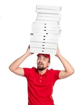 Перегруженный курьер в красной форме несёт на голове кучу коробок из-под пиццы, обеспечивая быструю доставку