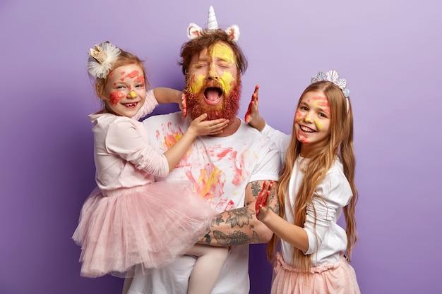生姜のひげを生やした過負荷の疲労シングルファーザーは、必死に泣き、2人の女性の子供と楽しんで、カラフルな絵の具を使用し、幸せな表情を持ち、紫色の壁の上に立っています。幸せな父の日のコンセプト