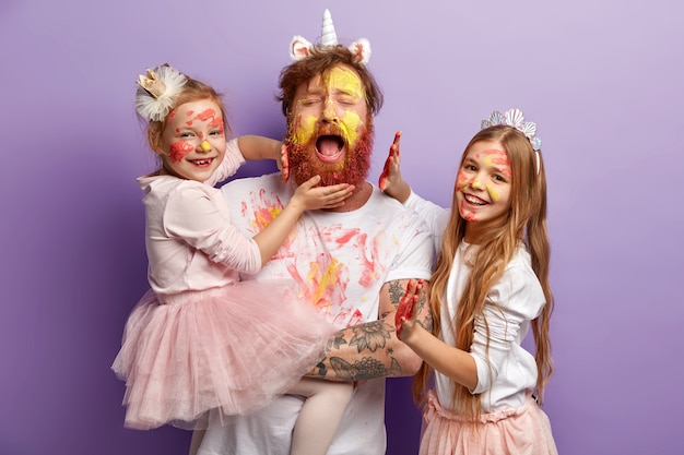 Overloaded fatigue single father with ginger beard, cries desperately, has fun with two female kids, use colourful paints, have happy expressions, stand over purple wall. happy fathers day concept