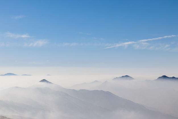 白い霧に覆われた山脈を見下ろす景色