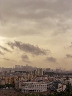 暗い雲のある建物でいっぱいの都会の景色を見下ろす