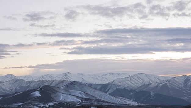 С видом на горы, покрытые снегом, с красивыми пейзажами заката в облачном небе.