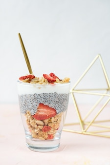 Overnight chia seed pudding with almond milk, yogurt, homemade granola, dried strawberries and almonds in a glass